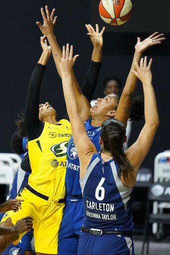Seattle Storm forward Alysha Clark, left, puts up what proved to be the game-winning shot over Minnesota Lynx forward Napheesa Collier and guard Bridget Carleton during the second half of Game 1 of a WNBA basketball semifinal round playoff series Tuesday, Sept. 22, 2020, in Bradenton, Fla.