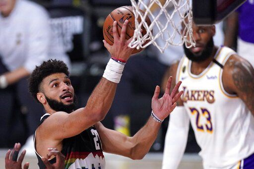 Denver Nuggets guard Jamal Murray, left, goes up for a shot attempt as Los Angeles Lakers' LeBron James, right rear, looks on during the second half of Game 3 of the NBA basketball Western Conference final Tuesday, Sept. 22, 2020, in Lake Buena Vista, Fla.