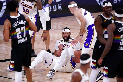 Denver Nuggets' Jamal Murray (27) looks on as Los Angeles Lakers' Anthony Davis (3) grabs his wrist after falling to the floor during play in the second half of Game 3 of the NBA basketball Western Conference final Tuesday, Sept. 22, 2020, in Lake Buena Vista, Fla.