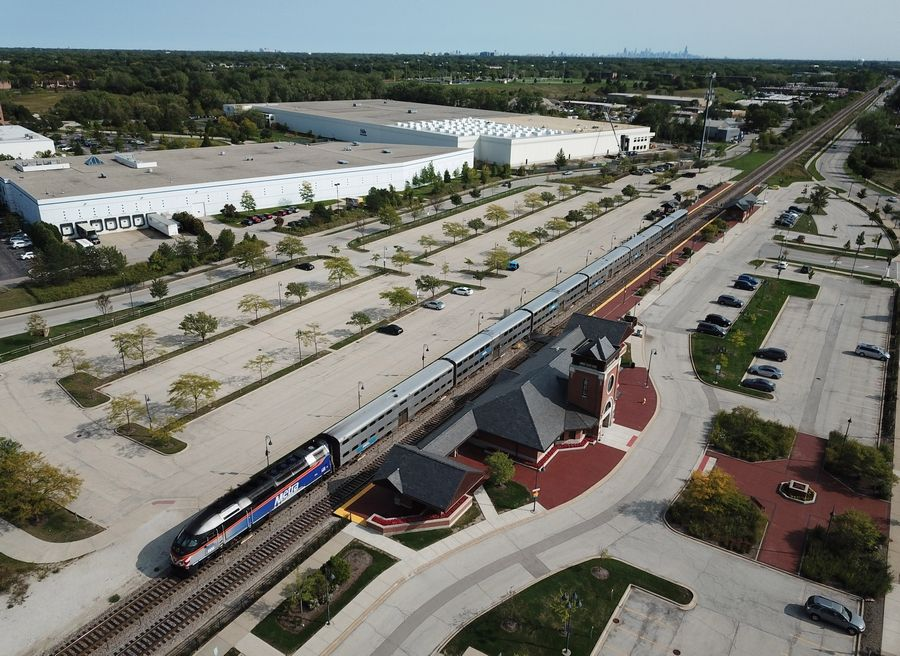 The stark reality of the COVID-19 pandemic in regard to Metra's ridership is displayed in this aerial view of the parking lot at The Glen/North Glenview station. Outbound Metra train number 2121 departs the station at 3:17 p.m. recently.