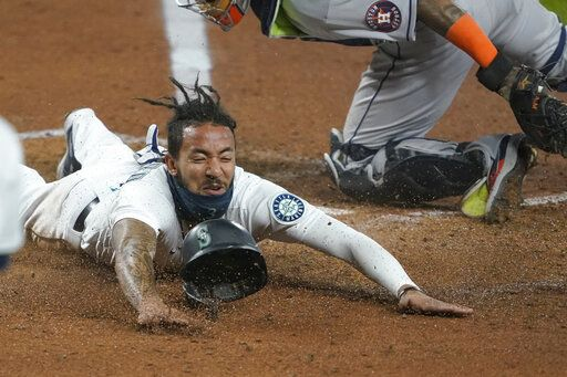 Seattle Mariners shortstop J.P. Crawford slides safely home past Houston Astros catcher Martin Maldonado during the fifth inning of a baseball game, Wednesday, Sept. 23, 2020, in Seattle. Crawford scored on a double hit by Kyle Seager.