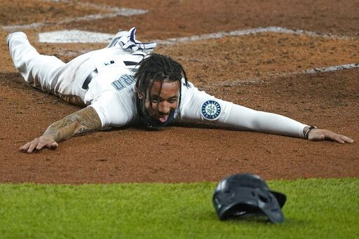 Seattle Mariners shortstop J.P. Crawford sprawls on the dirt and reacts after sliding safely home during the fifth inning of a baseball game against the Houston Astros, Wednesday, Sept. 23, 2020, in Seattle. Crawford scored on a double hit by Kyle Seager.