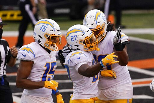 Los Angeles Chargers' Joshua Kelley (27) celebrates with teammates after rushing touchdown during the second half of an NFL football game against the Cincinnati Bengals, Sunday, Sept. 13, 2020, in Cincinnati.