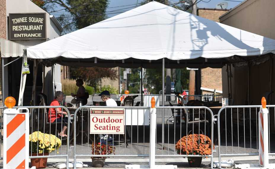 Diners enjoy the outdoor eating area at the Townee Square Restaurant Thursday morning in Libertyville. The village board has extended outdoor dining to May 1 and waived a requirement for fire sprinklers in tents.