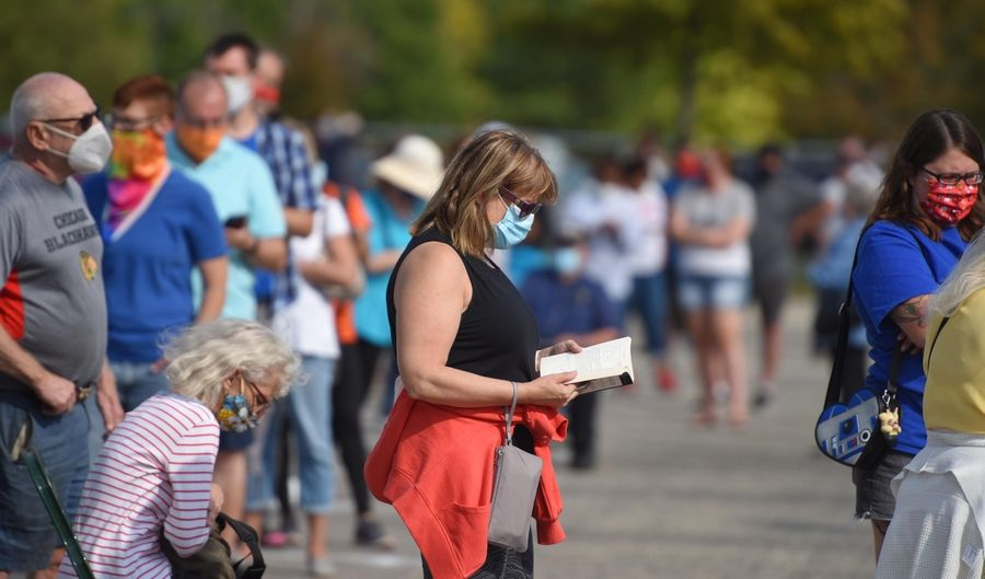 A woman reads a book as voters stand in line for almost three hours at the early voting polling place Thursday at the DuPage County Fairgrounds in Wheaton.