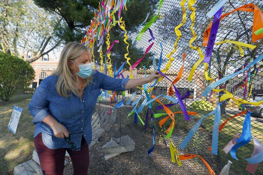 "Baird & Warner Northwest Suburban Broker Associate Tracy Bongiorno on Friday morning ties a ribbon to the ""wish tree"" interactive art display outside the real estate office in downtown Arlington Heights. ""We at Baird & Warner Northwest Suburban are really trying to pump people up,"" she said."