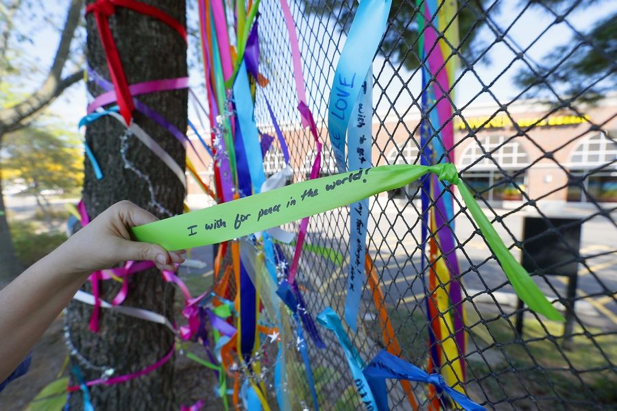 "Colorful ribbons tied to netting are in place at a ""wish tree"" in downtown Arlington Heights. Baird & Warner Northwest Suburban installed the 10-foot high, 35-foot wide banner Thursday and plans to keep it up through the weekend."