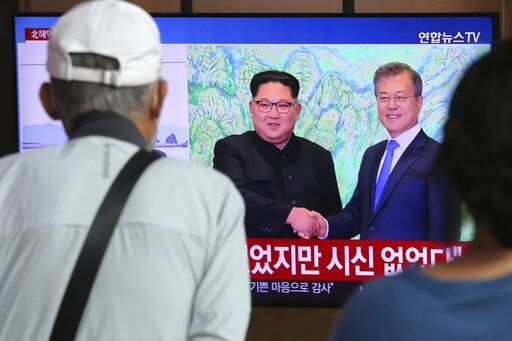 People watch a TV showing a file image of North Korean leader Kim Jong Un, left, and South Korean President Moon Jae-in during a news program at the Seoul Railway Station in Seoul, South Korea, Friday, Sept. 25, 2020. North Korean leader Kim apologized Friday over the killing of a South Korea official near the rivals' disputed sea boundary, saying he's 'œvery sorry'� about the incident he called unexpected and unfortunate, South Korean officials said.