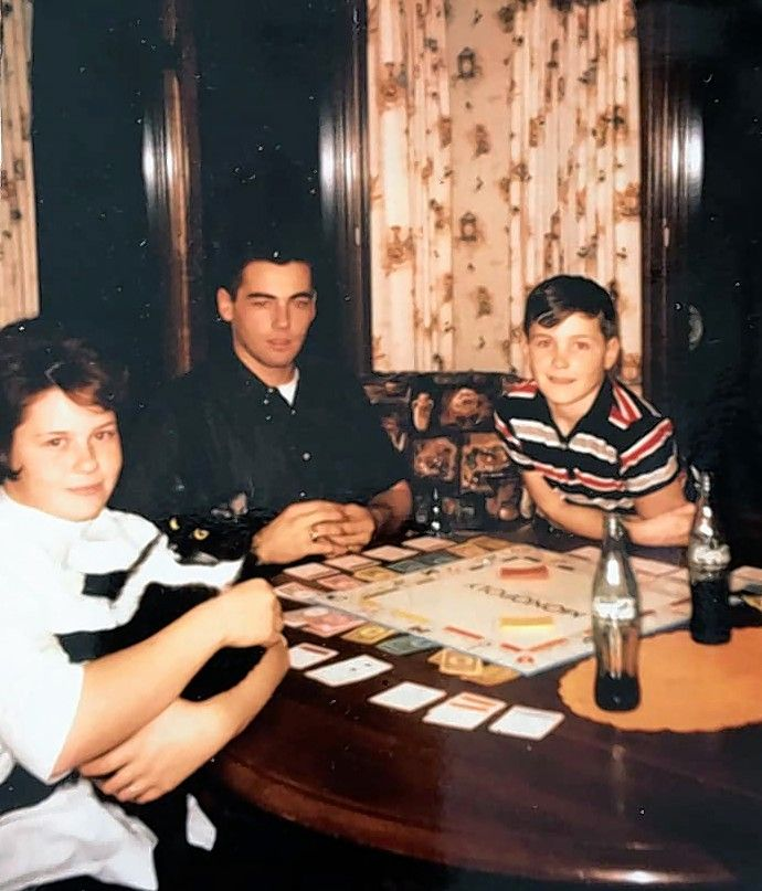 My sister Mary (holding Sheba the cat), from left, with brothers Nic and Rex, playing Monopoly in the kitchen about 1961, says Susan Anderson-Khleif.