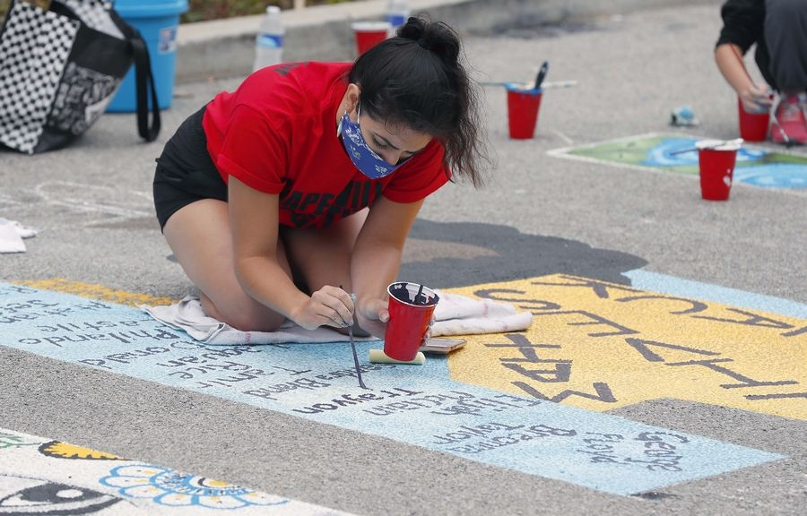 Rebecca Hernandez of Naperville puts the finishing touch on the letter H as the Art of Inclusion's first piece of inclusive-focused public art was painted on the Naperville Township parking lot Saturday.