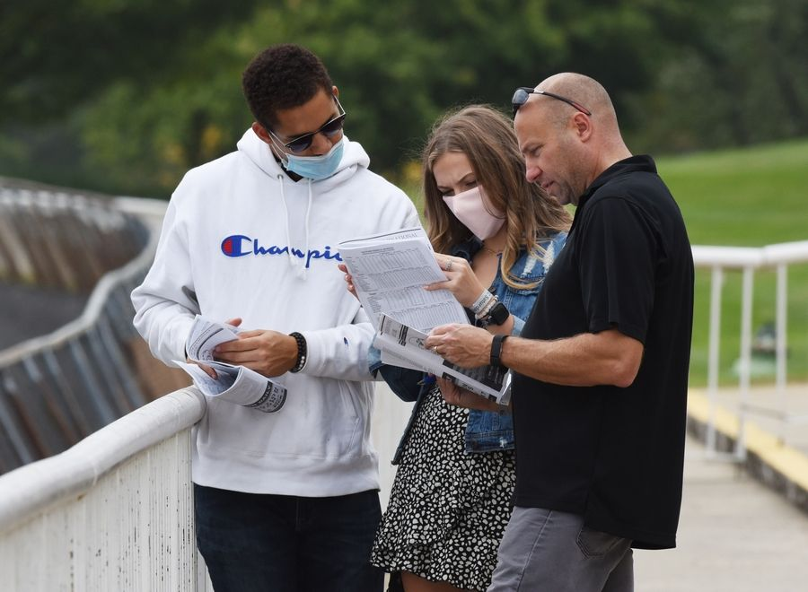 Jim Rojek, right, of Lake in the Hills his daughter, Haley, and Caleb Green of Denver view the racing program at Arlington Park Saturday.