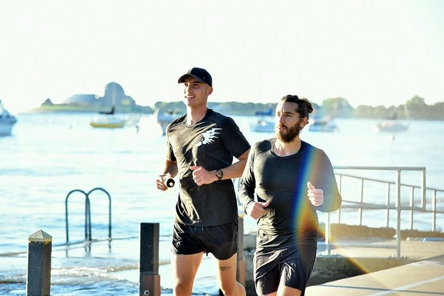 Running a variety of marathon routes during his quest to complete seven marathons in seven days, Lisle native Peter Krzywosz, left, runs along the Chicago lakefront with friend Cheyne Adam.