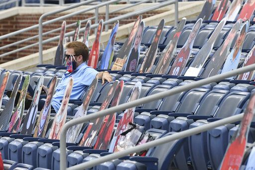 A fan sits among cardboard cutouts of other fans before the first half of an NCAA college football game between Mississippi and Florida in Oxford, Miss., Saturday, Sept. 26, 2020.