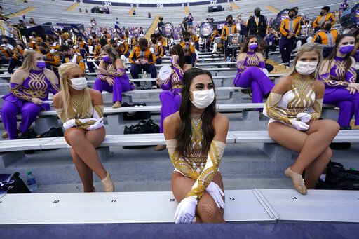 Members of the LSU Golden Girls dance team sit spaced apart wearing masks, under COVID-19 restrictions, requiring social distancing and masks, before an NCAA college football game between the LSU and the Mississippi State in Baton Rouge, La., Saturday, Sept. 26, 2020.