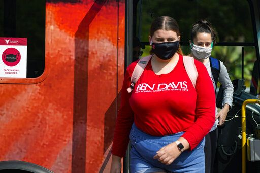 FILE - Masked students disembark from a bus on the campus of Ball State University in Muncie, Ind., Thursday, Sept. 10, 2020.    Colleges across the country are struggling to salvage the fall semester as campus coronavirus cases skyrocket and tensions with local health leaders flare. Schools have locked down dorms, imposed mask mandates, barred student fans from football games and toggled between online and in-person classes.