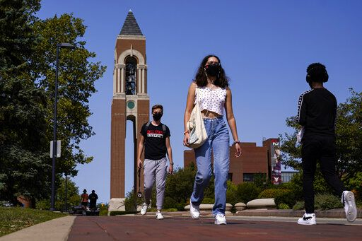 FILE - Masked students walk through the campus of Ball State University in Muncie, Ind., Thursday, Sept. 10, 2020.   Colleges across the country are struggling to salvage the fall semester as campus coronavirus cases skyrocket and tensions with local health leaders flare. Schools have locked down dorms, imposed mask mandates, barred student fans from football games and toggled between online and in-person classes.