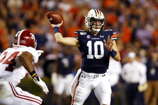FILE - In this Nov. 30, 2019, file photo, Auburn quarterback Bo Nix (10) throws a pass as Alabama linebacker Terrell Lewis (24) pressures during the second half of an NCAA college football game in Auburn, Ala.  Many major universities are determined to forge ahead despite warning signs about the virus, as evidenced by the expanding slate of college football games occurring Saturday. The football-obsessed SEC begins its season with fans in stadiums.