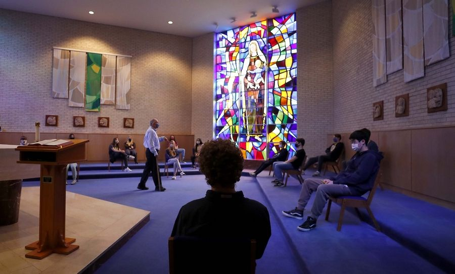 Deacon Mark Plaiss teaches in the chapel at Carmel Catholic High School in Mundelein, with students socially distanced.