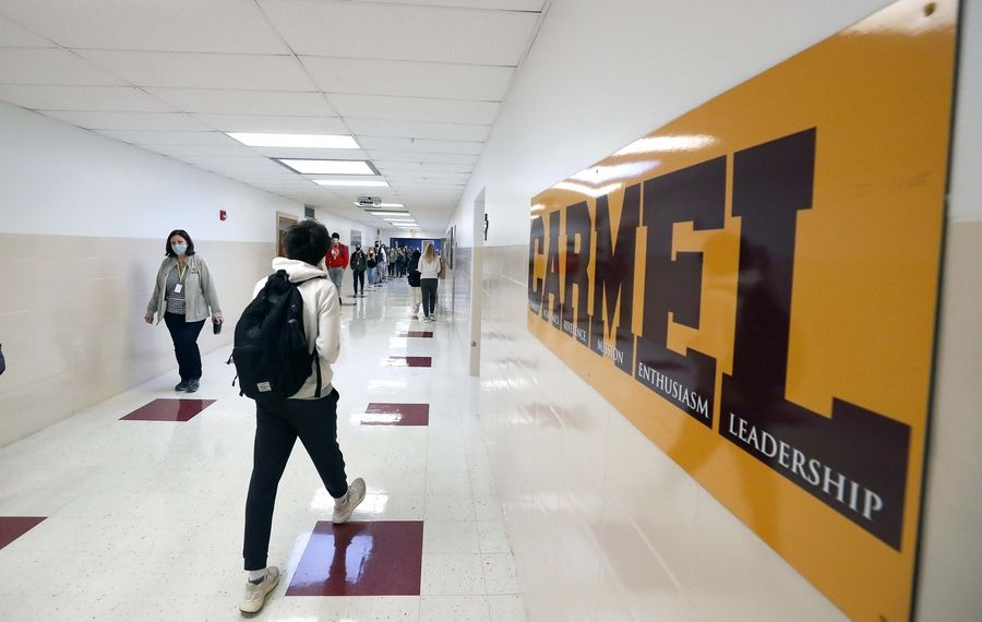 Students at Carmel Catholic High School in Mundelein keep socially distanced while walking through the hallways during passing periods this school year.
