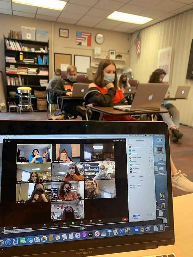 A class debate in French IV/V at Elgin Academy. Most of the students are in the classroom, but one of the debaters is using distance learning from home.