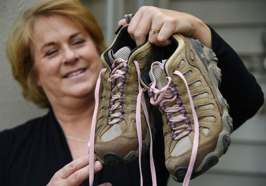 Leslie Ferris Yerger of Hawthorn Woods shows the hiking boots she wore during a 500-mile walk across Spain that she used to mentally prepare for her fight against breast cancer.