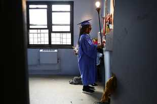 Maddison Washington, 11, stands at her bedroom mirror as she gets ready for her virtual graduation from her Brooklyn middle school, in the Brooklyn borough of New York. After being delayed twice, hundreds of thousands of elementary school students are heading back to classrooms Tuesday as New York City enters a high-stakes phase of resuming in-person learning during the coronavirus pandemic.
