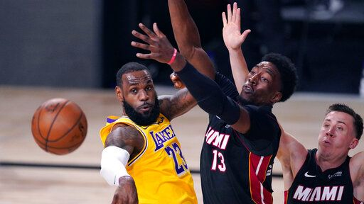 Los Angeles Lakers' LeBron James (23) passes the ball while pressured by Miami Heat's Bam Adebayo (13) during the second half of Game 1 of basketball's NBA Finals Wednesday, Sept. 30, 2020, in Lake Buena Vista, Fla.