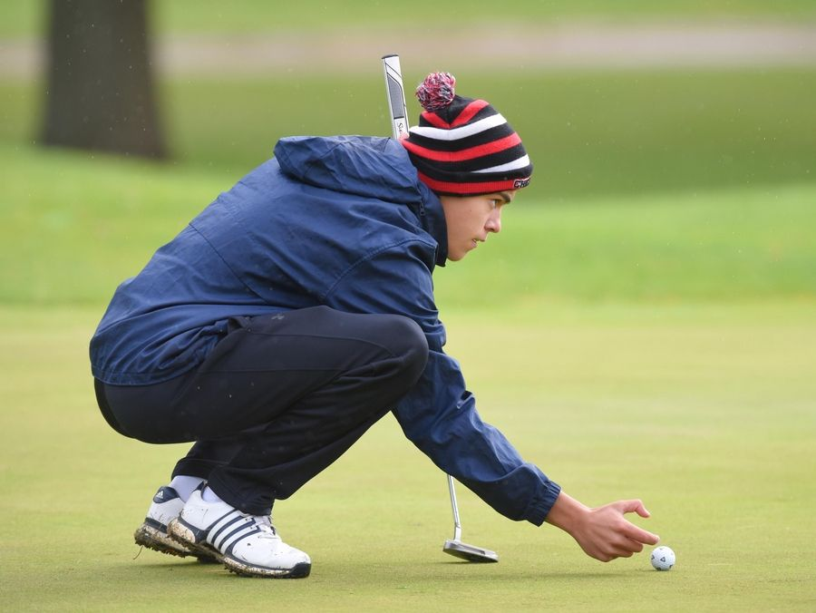 Crystal Lake Central's Christian Wakeford sets his ball at the Fox Valley Conference boys golf tournament at Randall Oaks Golf Course in West Dundee Thursday.