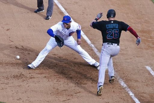 Miami Marlins' Garrett Cooper (26) grounds out as Chicago Cubs first baseman Anthony Rizzo handles the throw during the ninth inning in Game 2 of a National League wild-card baseball series Friday, Oct. 2, 2020, in Chicago.