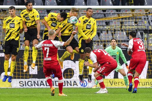 Freiburg's Jonathan Schmid, foreground, shoots a free kick during the German Bundesliga soccer match between Borussia Dortmund and SC Freiburg in Dortmund, Germany, Saturday, Oct. 3, 2020.