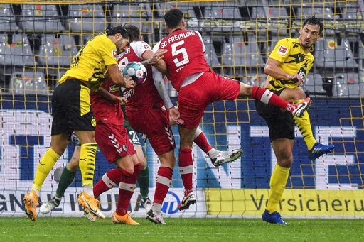 Borussia Dortmund and SC Freiburg players compete during their German Bundesliga soccer match in Dortmund, Germany, Saturday, Oct. 3, 2020.
