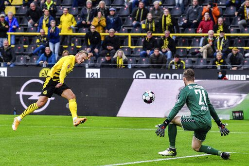 Dortmund's Erling Haaland, left, scores his second goal during the German Bundesliga soccer match between Borussia Dortmund and SC Freiburg in Dortmund, Germany, Saturday, Oct. 3, 2020.