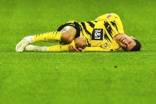 Dortmund's Giovanni Reyna grimaces in pain during the German Bundesliga soccer match between Borussia Dortmund and SC Freiburg in Dortmund, Germany, Saturday, Oct. 3, 2020.