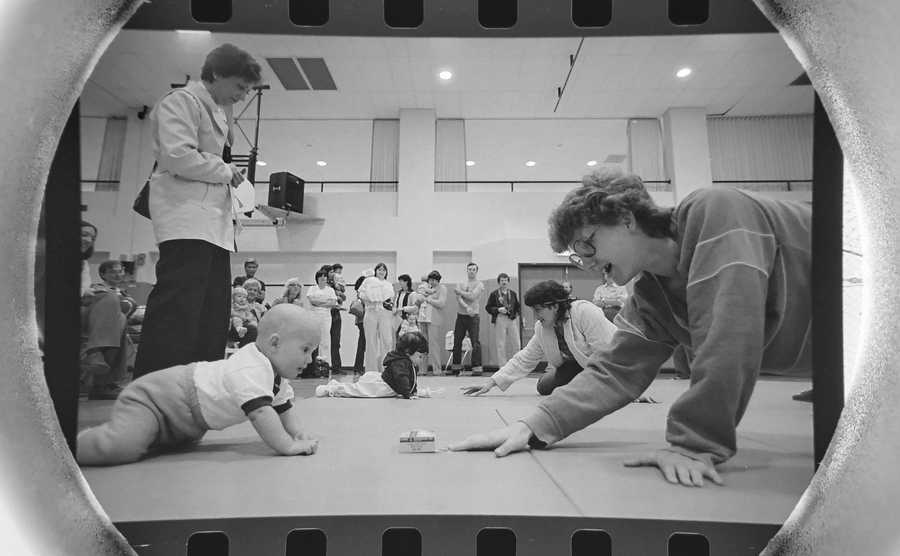 The Daily Herald Archive, Assignment # 63,253, Barry Jarvinen photo: A mother tries to coax her baby to the finish line during the Diaper Derby at the Community Recreation Center in Schaumburg in May of 1982.