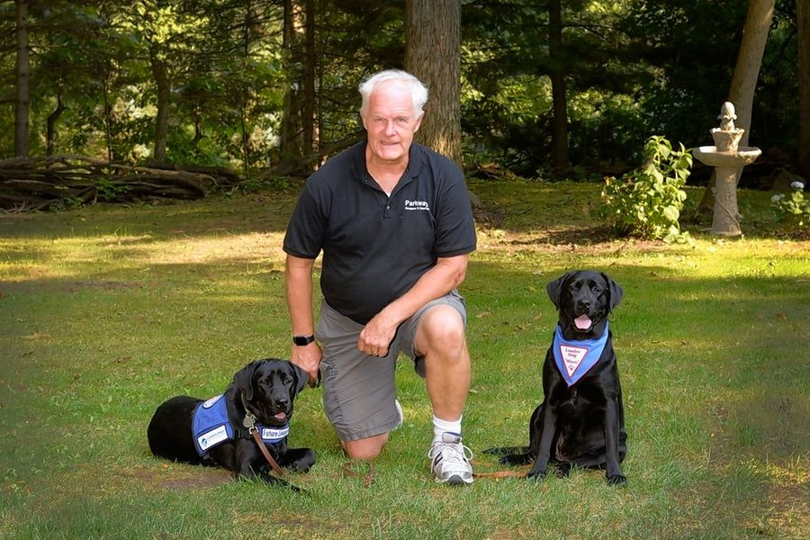 Jerry Ming of Grayslake with trainee Koko, 9 months, left, and mom Lucy, right. Koko is being trained to be a Leader Dog for a sight-impaired person. Mom Lucy has given birth to three litters of puppies for the program. After the fourth, she will belong to Jerry outright.
