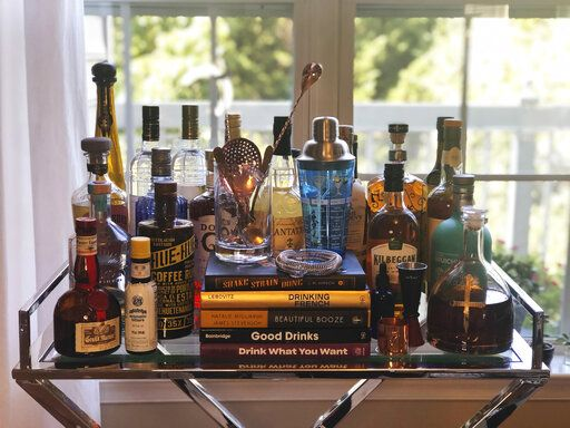 A collection of spirits and cocktail recipe books are displayed at a home in Alexandria, Va., on Oct. 4, 2020. Since the pandemic hit the United States, a lot of social drinking has moved back home. (Elizabeth Karmel via AP)