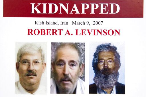 FILE - In this March 6, 2012, file photo, an FBI poster showing a composite image of former FBI agent Robert Levinson, right, of how he would look like now after five years in captivity, and an image, center, taken from the video, released by his kidnappers, and a picture before he was kidnapped, left, displayed during a news conference in Washington. A U.S. judge ordered Iran on Thursday, Oct. 1, 2020, to pay $1.45 billion to Levinson's family, who is believed to have been kidnapped by the Islamic Republic while on an unauthorized CIA mission to an Iranian island in 2007.