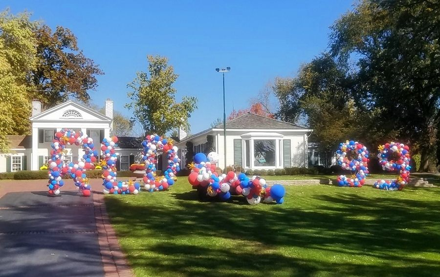 "A balloon arrangement reading ""RLD 99"" spells out the occasion Wednesday during a surprise parade to mark the 99th birthday of Arlington Park Chairman Emeritus Richard Duchossois outside his Barrington Hills home."
