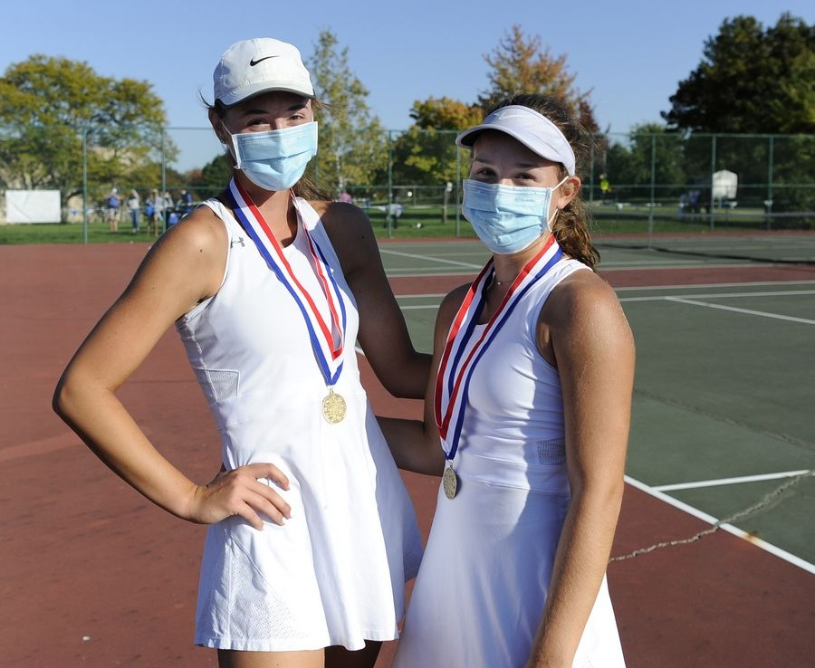 St. Charles North's Tatum Settelmyer and Leia Papanicholas claims first displaying their medals after winning the first doubles matchup at Lake Park High School West Campus on Thursday.