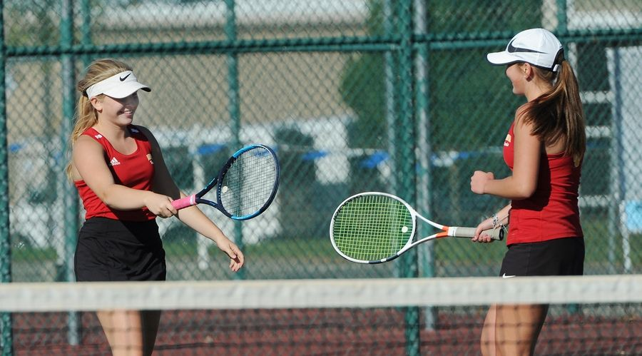 Batavia's Bella Lins (left) celebrates a point with tennis partner Leah Puttin as they played St. Charles North in the number one doubles match up at Lake Park High School West Campus on Thursday.