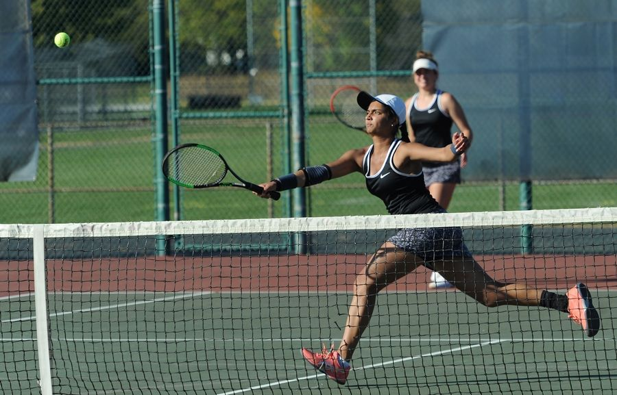 St. Charles East's Smita Dhar chases down a return from a Wheaton Warrenville South player in doubles tennis at Lake Park High School West Campus on Thursday.