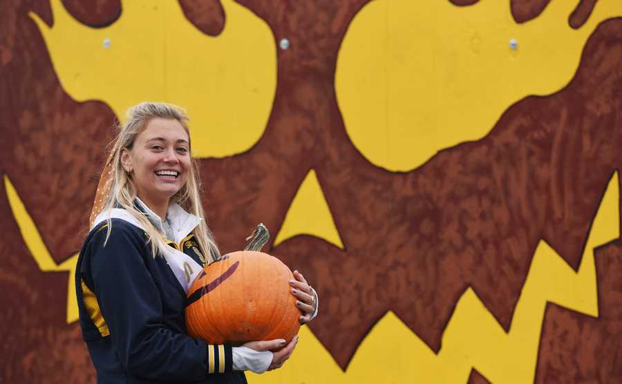 Senior Emmaline Schuh carries a pumpkin to the freshman float during the reverse parade at the Glenbrook South High School Fall Festival in Glenview Saturday, October 3, 2020.