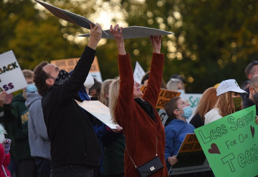 People show their signs to an overhead drone as Stevenson High School students, parents and supporters rally Monday for a return to school.