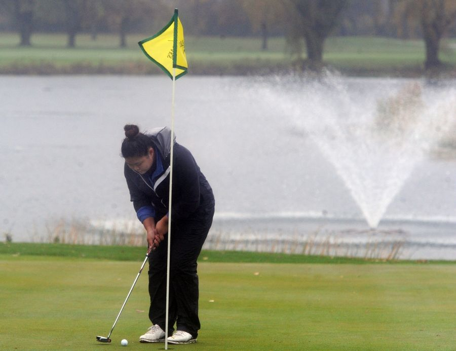 Emily Koh of Burlington Central sinks her putt on the fourteenth hole at girls sectional golf held at Randall Oaks Golf Club in West Dundee on Monday.