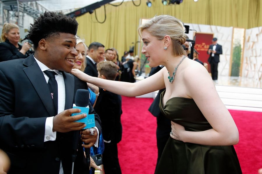 """Cheer"" star Jerry Harris, who has been charged with production of child pornography, talks with Greta Gerwig on the red carpet at the Oscars on Feb. 9 in Los Angeles. Harris is scheduled to appear in federal court Wednesday."