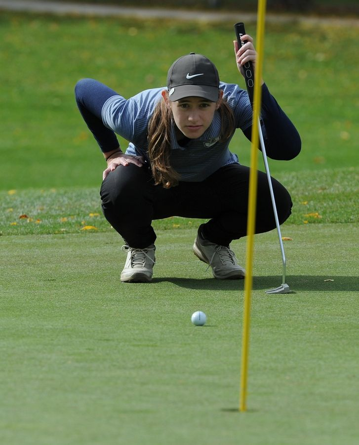 Glenbrook South's Maria Perakis eyes her ball position on the third green at the girls golf sectional at Arlington Lakes Golf Club in Arlington Heights on Tuesday.