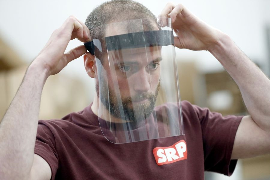 A worker tests a face shield to protect essential workers made at Standard Rubber Products Co. in Elk Grove Village.