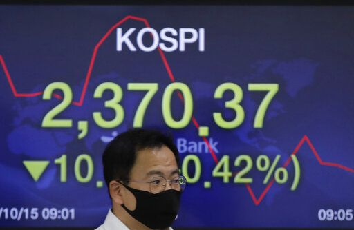 A currency trader walks by a screen showing the Korea Composite Stock Price Index (KOSPI) at the foreign exchange dealing room in Seoul, South Korea, Thursday, Oct. 15, 2020. Asian stocks followed Wall Street lower on Thursday as hopes U.S. leaders will agree on a new economic stimulus before the Nov. 3 presidential election faded.
