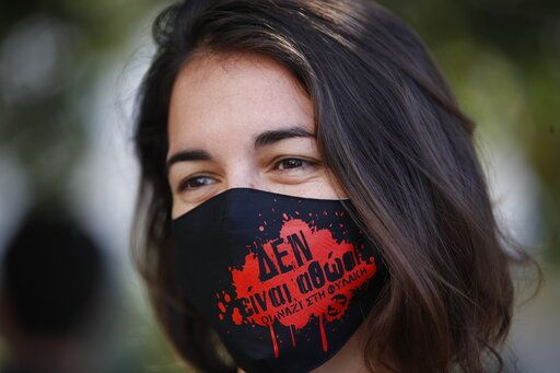 An anti-fascist protester, waring a mask to help prevent the spread of the coronavirus, gathers outside the court in Athens where the the sentencing announcement of the Golden Dawn trial, was schedule to be held, Wednesday, Oct. 14, 2020. The lengthy sentencing procedure is the final chapter in a more than five-year politically charged trial that encompassed four cases and involved 68 defendants, more than 200 witnesses and over 60 lawyers. The mask reads in Greek: 'Theyare not innocent, Nazis to prison'.