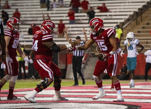 Louisiana-Lafayette running back Elijah Mitchell (15) and offensive lineman Shane Vallot (64) celebrate a touchdown by Mitchell during the second half of an NCAA college football game against Coastal Carolina in Lafayette, La., Wednesday, Oct. 14, 2020.